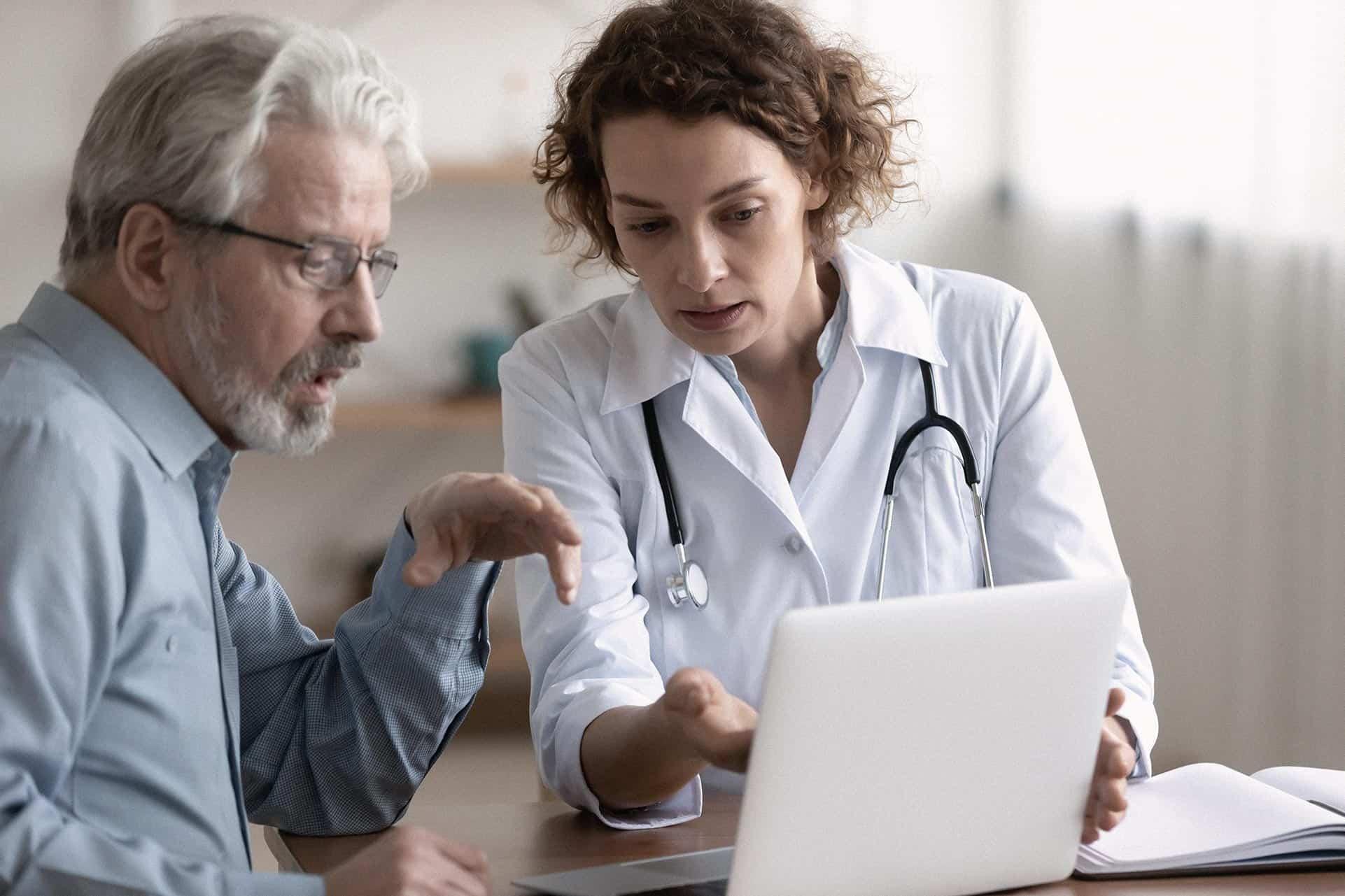 Een patient en een dokter bespreken informatie op een laptopscherm.